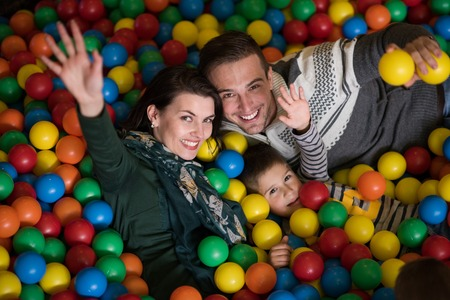 Happy young parents are playing with their kids at pool with colorful balls in a childrens playroom