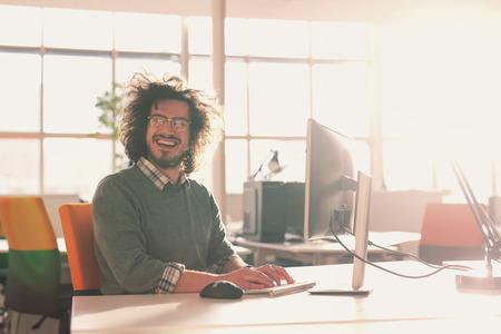 Jeune entrepreneur pigiste travaillant à l'aide d'un ordinateur dans l'espace Coworking Banque d'images - 81726987