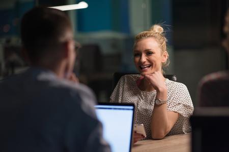 Equipe de negócios de inicialização multiétnica em reunião no brainstorming interior moderno do escritório noturno, trabalhando no laptop