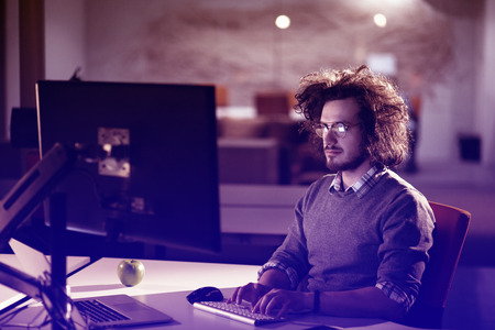 Young man working on computer at night in dark office. The designer works in the later time.