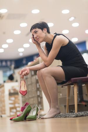 Woman Chooses  Shoes At Fashionable Shop Stock Photo
