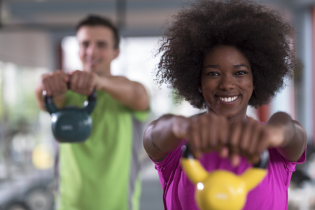 healthy couple  workout with weights lifting  dumbbels at  crossfit gym african  american woman with afro hairstyle