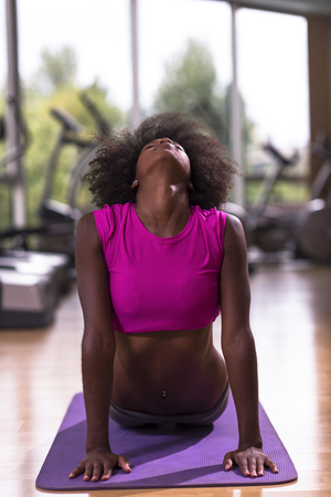 beautiful young african american woman exercise yoga in gym Stock Photo