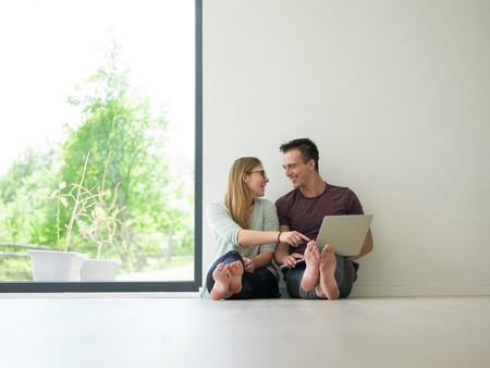 Young couple using laptop computer on the floor at luxury home together, looking at screen, smiling. Stock Photo