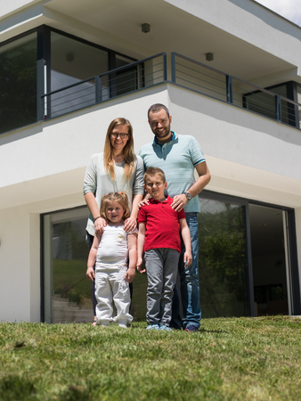Portrait of young happy family with children in the yard in front of their luxury home of villa photo
