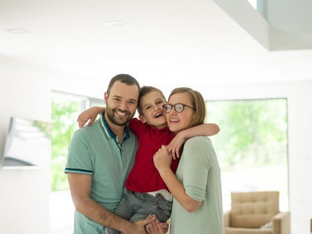 happy young family with little boy enjoys in the modern living room of their luxury home villa photo