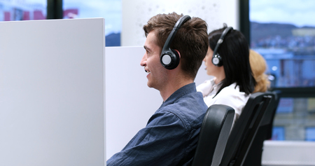 customer service representative: young smiling male call centre operator doing his job with a headset Stock Photo