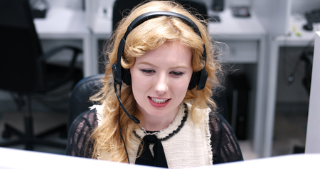 customer service representative: young smiling female call centre operator doing her job with a headset Stock Photo