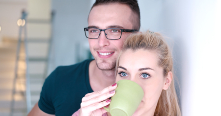romantic happy young couple enjoying morning coffee by the window in their luxury home Stock Photo