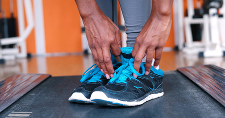 african american woman: Close up of running black female feet in sneakers in gym