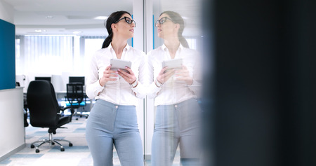 Pretty Businesswoman Using Tablet In front of Office Interior