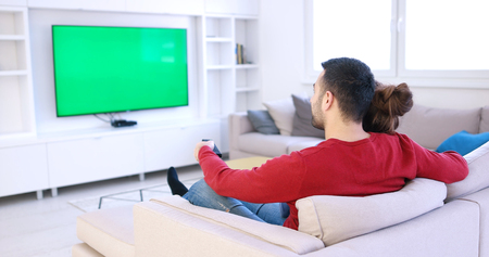 Pareja joven en el sofá viendo la televisión juntos en su casa de lujo Foto de archivo - 87128829