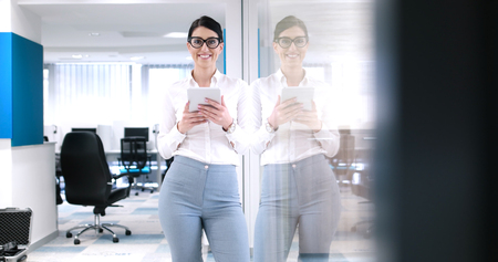 사무실 인테리어 앞에 태블릿을 사용하여 예쁜 사업가