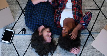 african american woman: Top view of attractive young multiethnic couple moving in, holding hands, looking at camera and smiling while lying among cardboard boxes Stock Photo