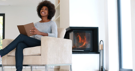 living room interior: Young beautiful african american woman sitting in front of fireplace at home on a cold autumn day and reading book