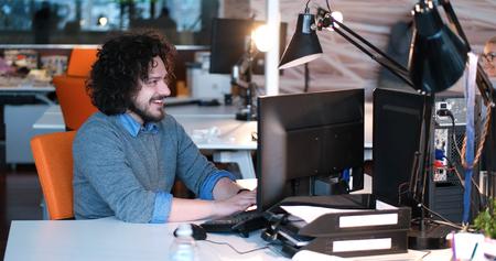 Jeune entrepreneur pigiste travaillant en utilisant un ordinateur dans coworking espace Banque d'images - 82505536