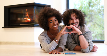 african american woman: beautiful young multiethnic couple with tablet computer showing a heart with their hands on the floor in front of fireplace at autumn day
