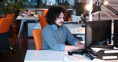 Jeune entrepreneur pigiste travaillant en utilisant un ordinateur dans coworking espace Banque d'images - 82495914