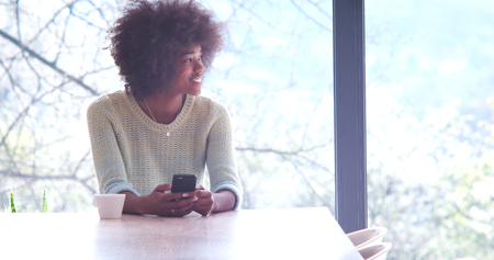 african student: Handsome young african american woman drinking coffee and using a mobile phone at  home