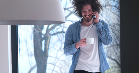 living room interior: Handsome casual young man drinking coffee and using a mobile phone at  home Stock Photo