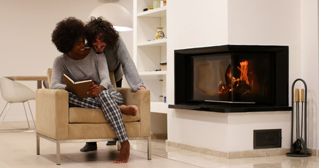 african american woman: Young beautiful multiethnic couple hugging in front of fireplace at home when reading a book at autumn day