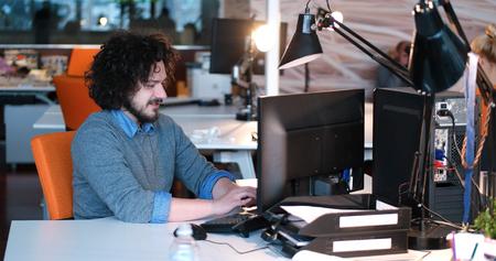Jeune entrepreneur pigiste travaillant en utilisant un ordinateur dans coworking espace Banque d'images - 82496098