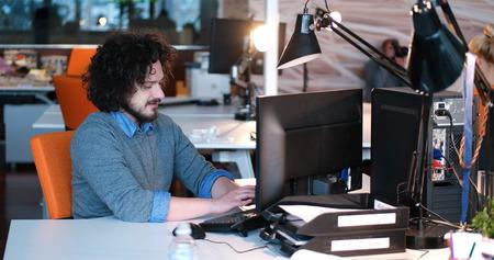 Jeune entrepreneur pigiste travaillant en utilisant un ordinateur dans coworking espace Banque d'images - 82495962