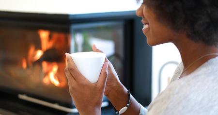 Afro-Amerikaanse vrouw het drinken kop koffie leesboek bij open haard. Jong zwart meisje met warme drank ontspannende verwarming warming up. herfst thuis.