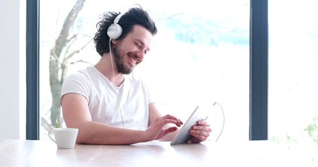 living room interior: Handsome young man listenig music on tablet at  home