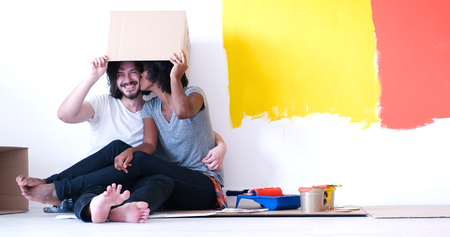 african american woman: Happy young multiethnic couple relaxing and playing with cardboard boxes after painting a room in their new house on the floor