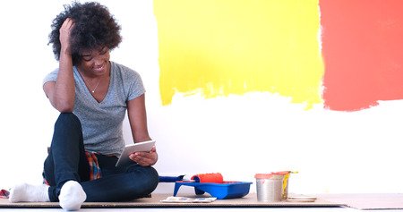 home decorating: Portrait of a beautiful african american female painter sitting on floor near wall after painting.