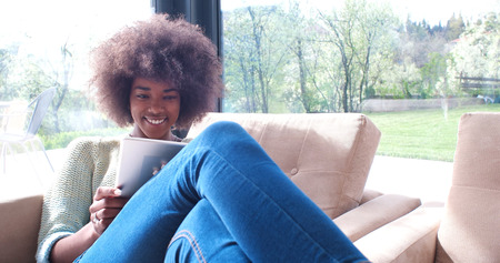 living room interior: Young african american woman at home relaxing in her luxury lliving room reading a digital tablet PC surf internet and work