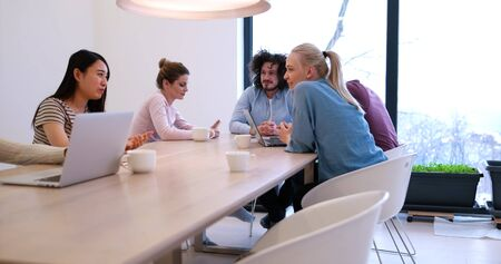 personas reunidas: Group of a young business people discussing business plan at modern startup office building Foto de archivo