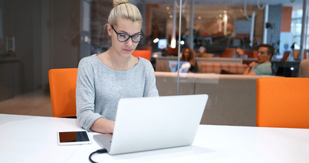Young female Entrepreneur Freelancer Working Using A Laptop In Coworking space Stock Photo