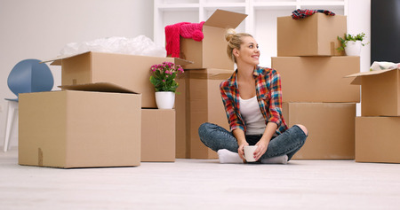 living room interior: people, moving new place and repair concept   happy beautiful  young woman with many cardboard boxes sitting on floor with Cup at home