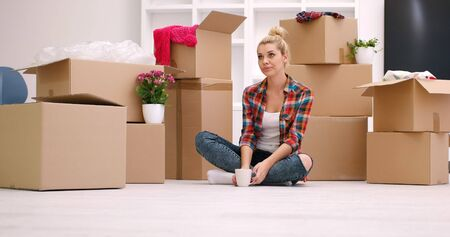 moving box: people, moving new place and repair concept   happy beautiful  young woman with many cardboard boxes sitting on floor with Cup at home