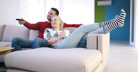 Young couple on the sofa watching television together in their luxury home Zdjęcie Seryjne - 85231531