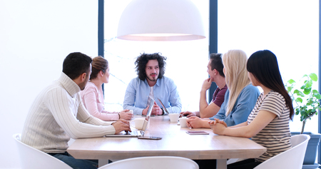 Group of a young business people discussing business plan at modern startup office building Stock Photo