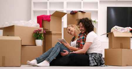 moving box: Relaxing in new house. Cheerful young couple sitting on the floor while cardboard boxes laying all around them