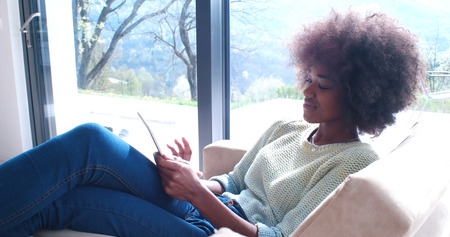 Young african american woman at home relaxing in her luxury lliving room reading a digital tablet PC surf internet and work