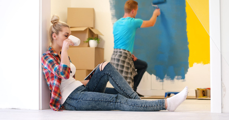 Happy couple doing home renovations, the man is painting the room and the woman is relaxing on the floor and connecting with a tablet Stock Photo