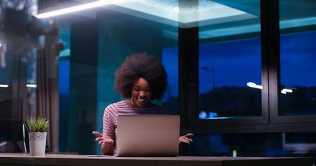 Jeune africaine agent féminin américain freelancer travaillant en utilisant un ordinateur portable dans l & # 39 ; espace de la nuit coworking Banque d'images - 82514679