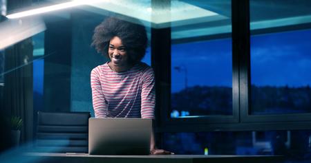 Jeune africaine agent féminin américain freelancer travaillant en utilisant un ordinateur portable dans l & # 39 ; espace de la nuit coworking Banque d'images - 82525277