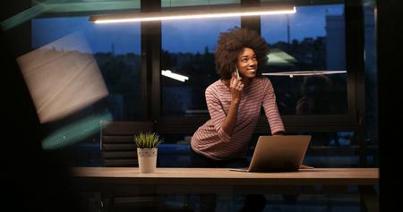 Jeune africaine agent féminin américain freelancer travaillant en utilisant un ordinateur portable dans l & # 39 ; espace de la nuit coworking Banque d'images - 82514795