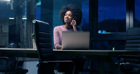 Jeune africaine agent féminin américain freelancer travaillant en utilisant un ordinateur portable dans l & # 39 ; espace de la nuit coworking Banque d'images - 82514797