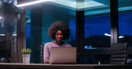 african student: Young african american female Entrepreneur Freelancer Working Using A Laptop In night Coworking space