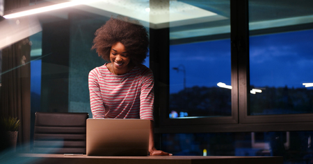 Young african american female Entrepreneur Freelancer Working Using A Laptop In night Coworking space