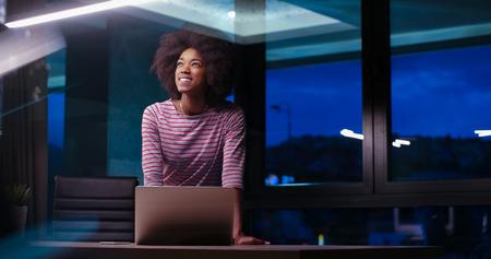 Jeune africaine agent féminin américain freelancer travaillant en utilisant un ordinateur portable dans l & # 39 ; espace de la nuit coworking Banque d'images - 82514968