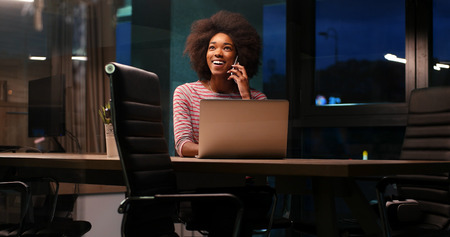 african american woman: Young african american female Entrepreneur Freelancer Working Using A Laptop In night Coworking space