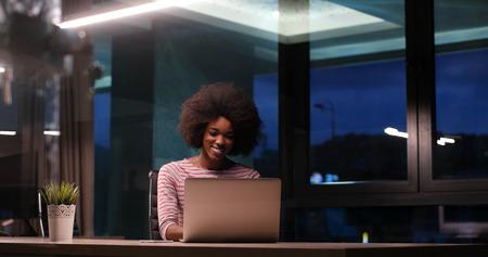 Jeune femme africaine américaine Entrepreneur Freelancer Travailler en utilisant un ordinateur portable En nuit Espace coworking Banque d'images - 82525199